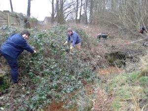 Students Sarah G and Josh clear ditch grate