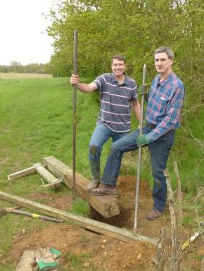 Triumphant volunteers by excavated post
