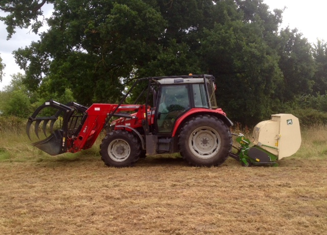 A large red tractor mowing the meadow.